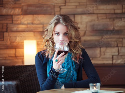 Beautiful Girl In Restaurant holding glass with red wine