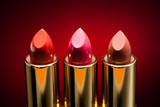 three lipsticks on red background