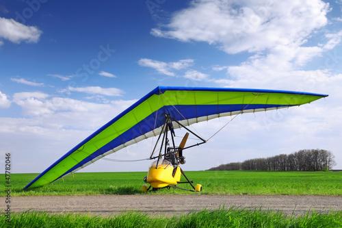 Leinwanddruck Bild Motorized hang glider over green grass