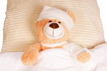 Teddy Bear with Bandage lying in the bed