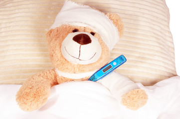 Teddy Bear with Bandage and thermometer lying in the bed