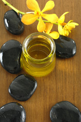 bottle of aromatherapy oil and black stones on board
