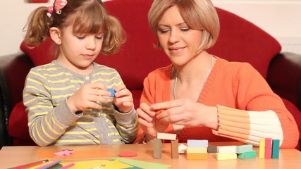 mother and daughter play with plasticine