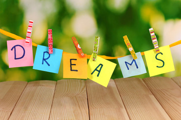 The word Dreams on wooden table on natural background