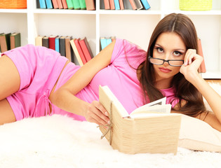 Young female relaxing on floor at home reading book