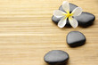 zen stones with frangipani flower arranged on bamboo board