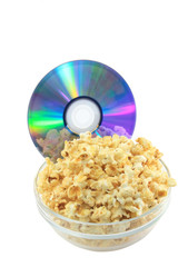Bowl full of caramel popcorn with DVD disk .