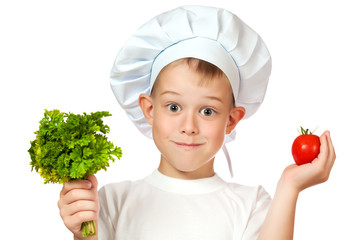 cute boy Chef is smiling. raw vegetables