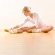 Beautiful ballet dancer stretching in the studio