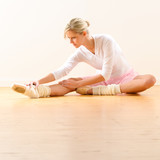 Beautiful ballet dancer stretching in the studio