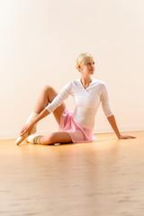 Beautiful ballerina sitting on floor holding ankle