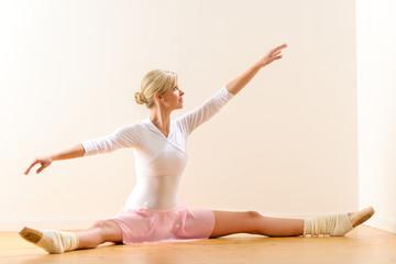 Ballet dancer lifting arms exercising in studio