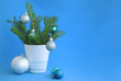christmas tree and decoration in a cup on a blue background