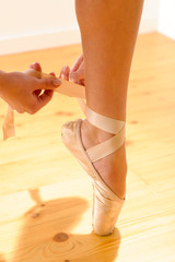 Close-up of ballerina tying her pointe shoe