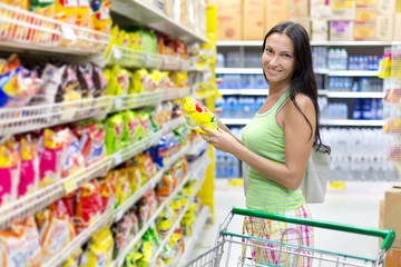Woman buys potato chips in the store