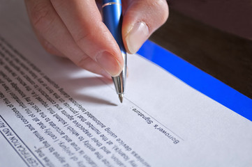 Concept of signing loan agreement with pen in hand