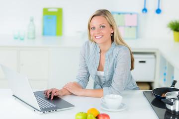 hausfrau mit computer in der küche