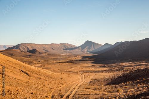 Leinwanddruck Bild Steinwüste mit Fahrspur