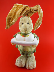 Straw rabbit with eggs in hands on red .