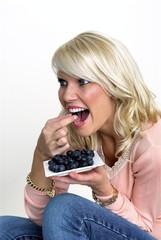 Junge blonde Frau isst  Blaubeeren