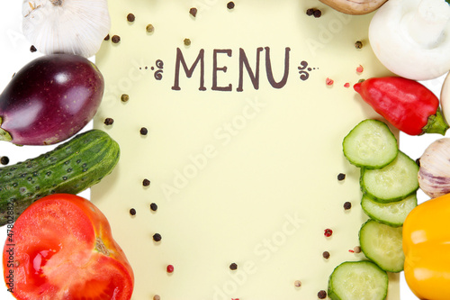 Menu surrounded by products and vegetables on yellow paper