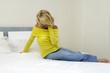 Junge blonde Frau sitzt traurig auf dem Bett