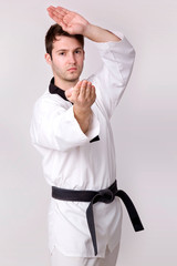 Young man practicing martial arts over grey background