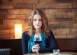 Portrait of pretty girl in restaurant holding glass with wine