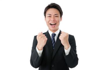 両手でガッツポーズをする若いビジネスマン