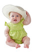 Baby girl in green dress sits wearing big straw hat