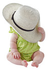 Baby girl in green dress plays peekaboo with  big straw hat