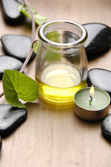 Green leaf and stones and bottle of aromatherapy oil