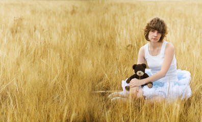 The sad girl in the field with a bear in a hand