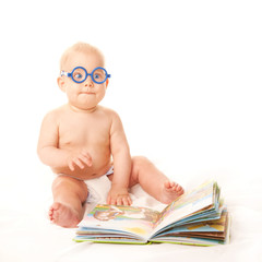 Baby in glasses reading book and learning.