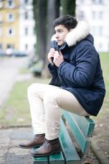 Attraktiver Mann sitzt auf einer Bank