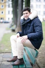 Hübscher Mann auf einer Bank sitzend