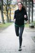 Junge Frau joggt durch den Park