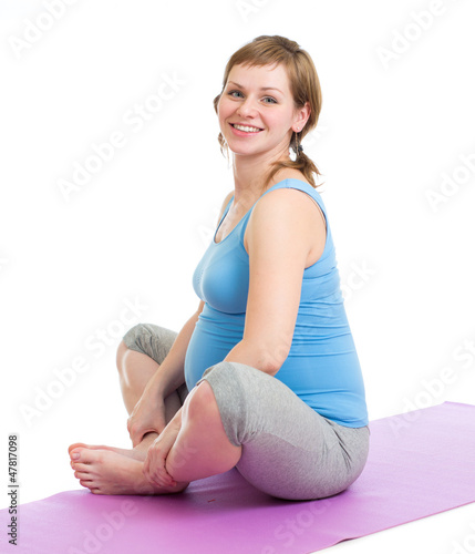 Pregnant woman doing gymnastic exercises isolated  on white