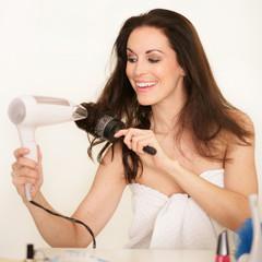 Hübsche Frau föhnt ihre Haare