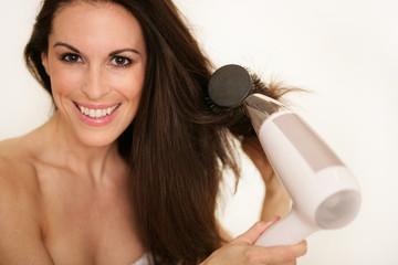 Attraktive Frau beim Haareföhnen