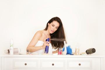 Frau beim Stylen mit Haarspray