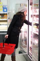 Frau steht im Supermarkt vor dem Kühlregal