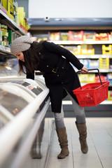 Frau kauft Pizza aus dem Tiefkühlregal