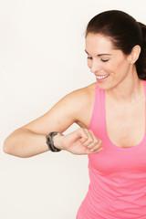 Hübsche Sportlerin schaut auf die Uhr