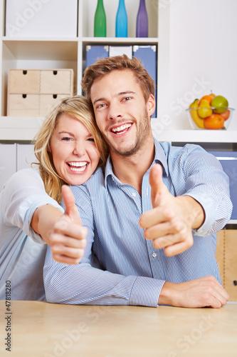 Paar im Wohnzimmer hält Daumen hoch