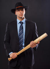 Serious man in a suit holding a bat