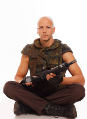 Hairless soldier sitting with rifle in hands