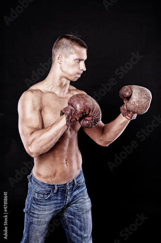 Young man with muscles in boxing gloves
