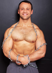 Strong man with muscles related by chain