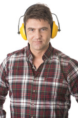 Serious handyman with earmuffs on white background
